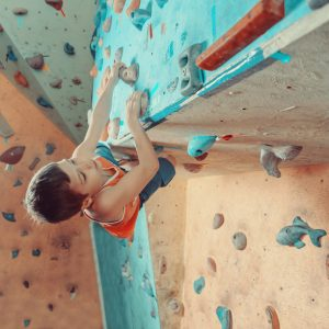 Free climber boy climbing on artificial boulders in gym